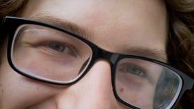 Στενό μήκος σε πόδηα των όμορφων ματιών ατόμων ` s στα γυαλιά που εξετάζουν τη κάμερα και που χαμογελούν, έξυπνο βλέμμα του επιτυ απόθεμα βίντεο