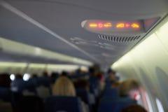 Στερεώστε τις ζώνες ασφαλείας και τα σημάδια απαγόρευσης του καπνίσματος στο αεροπλάνο Στοκ Φωτογραφίες