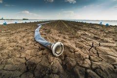 Στεριά - ξηρασία - και μάνικα για το πότισμα στοκ φωτογραφία