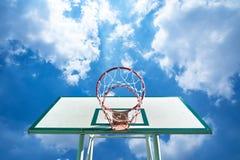 Στεφάνη καλαθοσφαίρισης σε έναν μπλε ουρανό με τα σύννεφα Στοκ Εικόνες