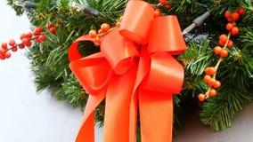 Στεφάνι έλατου Χριστουγέννων με την κόκκινη κορδέλλα και τους κόκκινους κλάδους των μούρων Ντεκόρ παραδοσιακών Χριστουγέννων και  απόθεμα βίντεο
