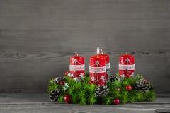 Στεφάνι ή κορώνα εμφάνισης με τέσσερα κόκκινα κεριά στο ξύλινο backgroun στοκ φωτογραφίες