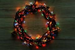 Στεφάνι γιρλαντών Χριστουγέννων στο γκρίζο ξύλινο υπόβαθρο Στοκ Εικόνες