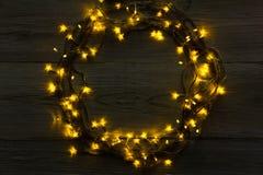 Στεφάνι γιρλαντών Χριστουγέννων στο γκρίζο ξύλινο υπόβαθρο Στοκ εικόνα με δικαίωμα ελεύθερης χρήσης