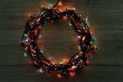 Στεφάνι γιρλαντών Χριστουγέννων στο γκρίζο ξύλινο υπόβαθρο Στοκ φωτογραφία με δικαίωμα ελεύθερης χρήσης