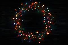 Στεφάνι γιρλαντών Χριστουγέννων στο σκοτεινό ξύλινο υπόβαθρο Στοκ Εικόνα