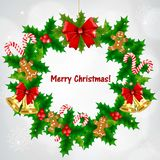 Στεφάνι ελαιόπρινου Χριστουγέννων με τα χρυσά κουδούνια και κόκκινο τόξο στο χιονώδες υπόβαθρο απεικόνιση αποθεμάτων