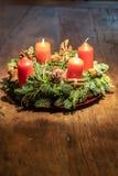 Στεφάνι εμφάνισης και δύο καίγοντας κόκκινα κεριά σε ένα ξύλινο επιτραπέζιο στούντιο στοκ εικόνες