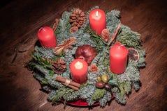 Στεφάνι εμφάνισης και δύο καίγοντας κόκκινα κεριά σε ένα ξύλινο επιτραπέζιο στούντιο στοκ εικόνα με δικαίωμα ελεύθερης χρήσης