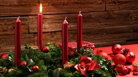 Στεφάνι εμφάνισης με ένα καίγοντας κερί και εορταστική διακόσμηση μπροστά από έναν εκλεκτής ποιότητας ξύλινο τοίχο Στοκ φωτογραφία με δικαίωμα ελεύθερης χρήσης