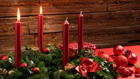 Στεφάνι εμφάνισης με δύο καίγοντας κεριά και εορταστική διακόσμηση μπροστά από έναν εκλεκτής ποιότητας ξύλινο τοίχο Στοκ φωτογραφία με δικαίωμα ελεύθερης χρήσης