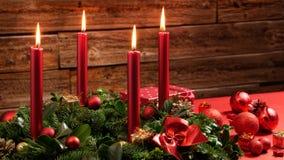 Στεφάνι εμφάνισης με τέσσερα καίγοντας κεριά και εορταστική διακόσμηση μπροστά από έναν εκλεκτής ποιότητας ξύλινο τοίχο Στοκ εικόνες με δικαίωμα ελεύθερης χρήσης