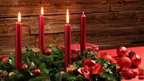 Στεφάνι εμφάνισης με τρία καίγοντας κεριά και εορταστική διακόσμηση μπροστά από έναν εκλεκτής ποιότητας ξύλινο τοίχο Στοκ Εικόνα