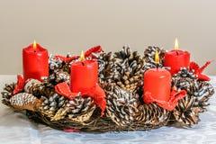 Στεφάνι εμφάνισης Χριστουγέννων με τα κόκκινα κεριά Στοκ Φωτογραφία