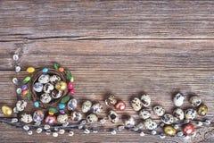 Στεφάνι ιτιών Πάσχας και ζωηρόχρωμα αυγά Πάσχας ορτυκιών στο παλαιό ξύλινο υπόβαθρο Τοπ άποψη, διάστημα αντιγράφων Στοκ Φωτογραφίες