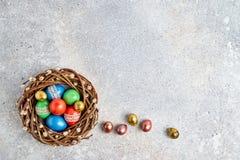 Στεφάνι ιτιών Πάσχας και ζωηρόχρωμα αυγά Πάσχας στο γκρίζο υπόβαθρο Τοπ άποψη, διάστημα αντιγράφων Στοκ Φωτογραφίες