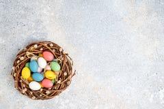 Στεφάνι ιτιών Πάσχας και ζωηρόχρωμα αυγά Πάσχας στο γκρίζο υπόβαθρο Τοπ άποψη, διάστημα αντιγράφων Στοκ εικόνα με δικαίωμα ελεύθερης χρήσης