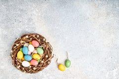 Στεφάνι ιτιών Πάσχας και ζωηρόχρωμα αυγά Πάσχας στο γκρίζο υπόβαθρο Τοπ άποψη, διάστημα αντιγράφων Στοκ Εικόνες