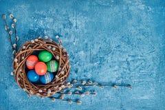 Στεφάνι ιτιών Πάσχας και ζωηρόχρωμα αυγά Πάσχας στο μπλε υπόβαθρο Τοπ άποψη, διάστημα αντιγράφων Στοκ Εικόνα