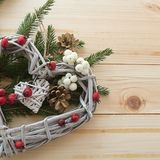 Στεφάνι καρδιών Χριστουγέννων με τα χειμερινά μούρα και τους κλάδους ενός Chr στοκ εικόνα