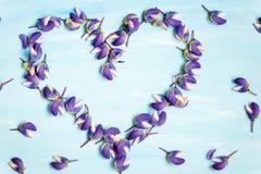 Στεφάνι καρδιών των πορφυρών πετάλων και των λουλουδιών lupines στο σκοτεινό ξύλινο υπόβαθρο Στοκ φωτογραφία με δικαίωμα ελεύθερης χρήσης