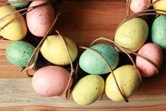Στεφάνι Πάσχας άνοιξη με τα ζωηρόχρωμα αυγά στο ανοικτό καφέ υπόβαθρο στοκ εικόνες με δικαίωμα ελεύθερης χρήσης