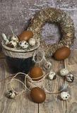Στεφάνι Πάσχας, αυγά σε ένα δοχείο αργίλου, καφετιά αυγά, αυγά ορτυκιών, φτερά κοτόπουλου, Στοκ Εικόνες