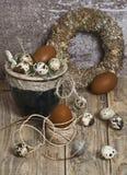 Στεφάνι Πάσχας, αυγά σε ένα δοχείο αργίλου, καφετιά αυγά, αυγά ορτυκιών, φτερά κοτόπουλου, Στοκ φωτογραφία με δικαίωμα ελεύθερης χρήσης