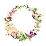 Στεφάνι Πάσχας με το λαγουδάκι Πάσχας, χρωματισμένα αυγά στη χλόη, λουλούδια Σύνορα κύκλων watercolor Στοκ Εικόνες