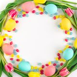 Στεφάνι Πάσχας φιαγμένο από κίτρινες τουλίπες, ζωηρόχρωμες αυγά και καραμέλες στο άσπρο υπόβαθρο r στοκ εικόνα με δικαίωμα ελεύθερης χρήσης