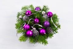 Στεφάνι πορτών Χριστουγέννων με τους ασημένιους κώνους πεύκων και τα πορφυρά μπιχλιμπίδια Στοκ εικόνα με δικαίωμα ελεύθερης χρήσης