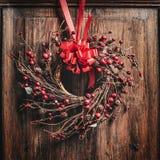Στεφάνι Χριστουγέννων με την κόκκινη κορδέλλα και μούρα σε ξύλινο Στοκ φωτογραφία με δικαίωμα ελεύθερης χρήσης