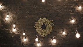 Στεφάνι Χριστουγέννων με τη γιρλάντα στον ξύλινο τοίχο φιλμ μικρού μήκους