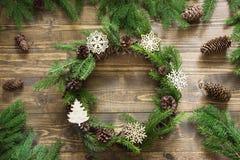 Στεφάνι Χριστουγέννων με τους κλάδους έλατου και διακοσμητικά snowflakes ξύλινο tabletop Επίπεδος βάλτε Στοκ Φωτογραφίες