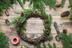 Στεφάνι Χριστουγέννων με τους κλάδους έλατου και κώνος πεύκων ξύλινο tabletop Επίπεδος βάλτε Στοκ φωτογραφία με δικαίωμα ελεύθερης χρήσης