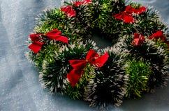 Στεφάνι Χριστουγέννων με το κόκκινο τόξο σε ένα μπλε υπόβαθρο στοκ εικόνες