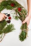Στεφάνι Χριστουγέννων που κάνει από τη γυναίκα Στοκ Εικόνα