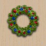 Στεφάνι Χριστουγέννων Πράσινος κλάδος του έλατου με τις κόκκινα, μπλε σφαίρες και snowflakes σε ένα υπόβαθρο του ξύλου cards chri Στοκ εικόνα με δικαίωμα ελεύθερης χρήσης
