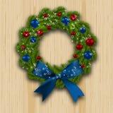 Στεφάνι Χριστουγέννων Πράσινος κλάδος του έλατου με τις κόκκινες, μπλε σφαίρες και του μπλε τόξου στο ξύλινο υπόβαθρο cards chris Στοκ φωτογραφία με δικαίωμα ελεύθερης χρήσης