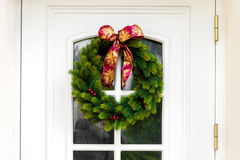 Στεφάνι Χριστουγέννων πόρτες στις άσπρες σπιτιών Στοκ Εικόνες
