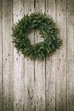 Στεφάνι Χριστουγέννων στην ξύλινη ανασκόπηση Στοκ φωτογραφία με δικαίωμα ελεύθερης χρήσης