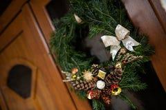 Στεφάνι Χριστουγέννων στην ξύλινη μπροστινή πόρτα στοκ εικόνα με δικαίωμα ελεύθερης χρήσης