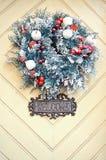 Στεφάνι Χριστουγέννων στην ξύλινη διακόσμηση πορτών στενός κόκκινος χρόνος Χριστουγέννων ανασκόπησης επάνω Στοκ Εικόνα