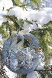 Στεφάνι Χριστουγέννων στους κλάδους των ερυθρελατών που καλύπτονται με το χιόνι Στοκ Φωτογραφία