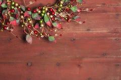 Στεφάνι Χριστουγέννων στο κόκκινο ξύλινο υπόβαθρο grunge Στοκ Φωτογραφίες