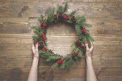 Στεφάνι Χριστουγέννων των κομψών κλάδων με τα μούρα ελαιόπρινου στον ξύλινο πίνακα Θηλυκό στεφάνι εκμετάλλευσης χεριών Τοπ όψη Στοκ φωτογραφίες με δικαίωμα ελεύθερης χρήσης