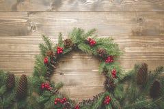 Στεφάνι Χριστουγέννων των κομψών κλάδων με τα μούρα ελαιόπρινου στον ξύλινο πίνακα Επίπεδος βάλτε Τοπ όψη εικόνα που τονίζεται Στοκ εικόνες με δικαίωμα ελεύθερης χρήσης