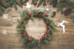 Στεφάνι Χριστουγέννων των κομψών κλάδων με τα μούρα ελαιόπρινου στον ξύλινο πίνακα Επίπεδος βάλτε Τοπ όψη Στοκ Φωτογραφίες