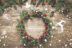 Στεφάνι Χριστουγέννων των κομψών κλάδων με τα μούρα ελαιόπρινου στον ξύλινο πίνακα Επίπεδος βάλτε Τοπ όψη Στοκ Εικόνες
