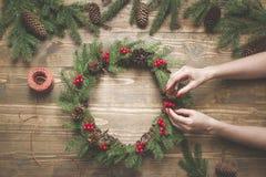 Στεφάνι Χριστουγέννων φιαγμένο από κομψούς κλάδους με τα μούρα ελαιόπρινου στον ξύλινο πίνακα Θηλυκό διακοσμημένο χέρι στεφάνι Το Στοκ Εικόνα